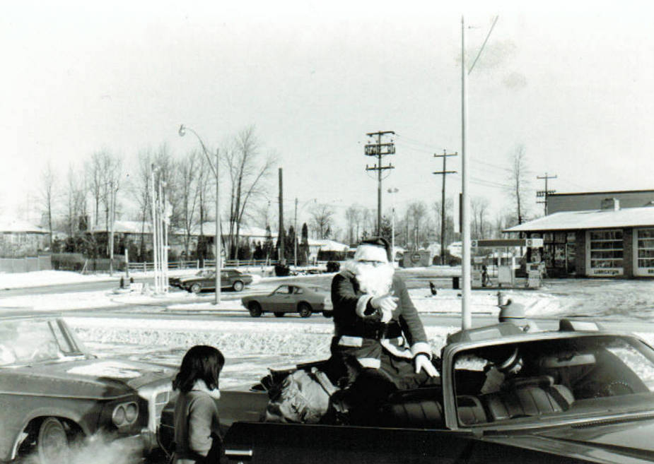 Santa Clause rides in open convertible for MWHA Christmas Caravan & Food Drive in the 1970's