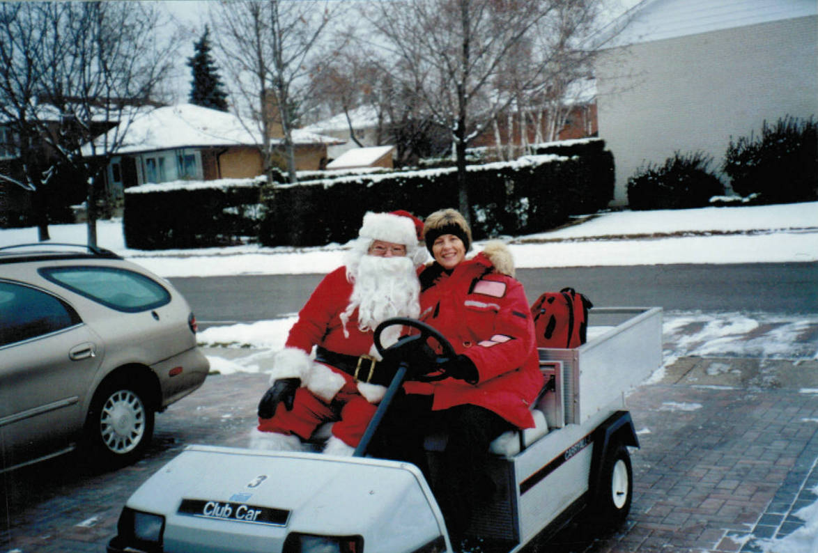 Santa Clause rides in Markland Wood Golf Club cart during MWHA Christmas Caravan & Food Drive in the 1980's